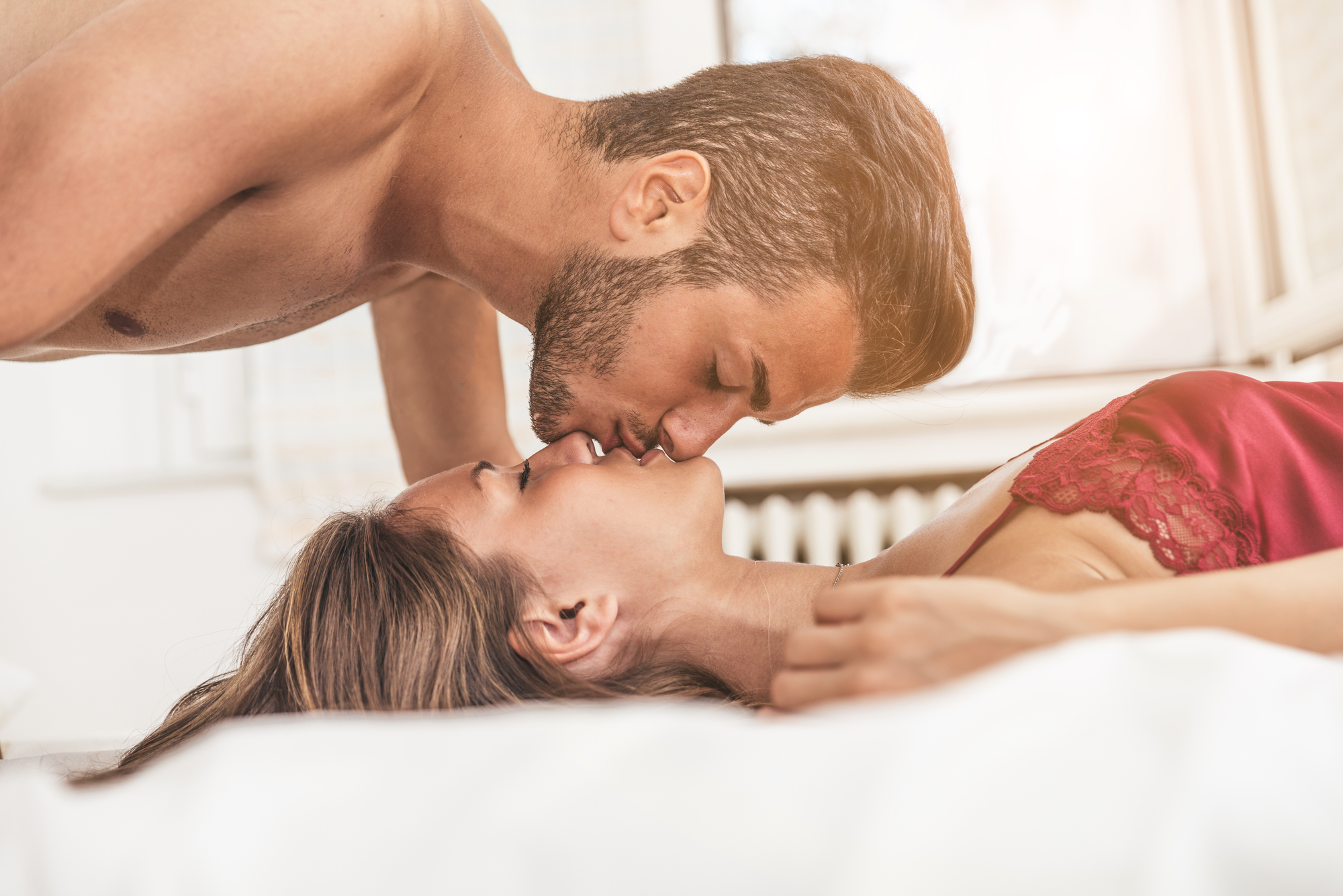 Young beautiful couple on a bed - Two lovers in the sleeping room, kissing on the bed