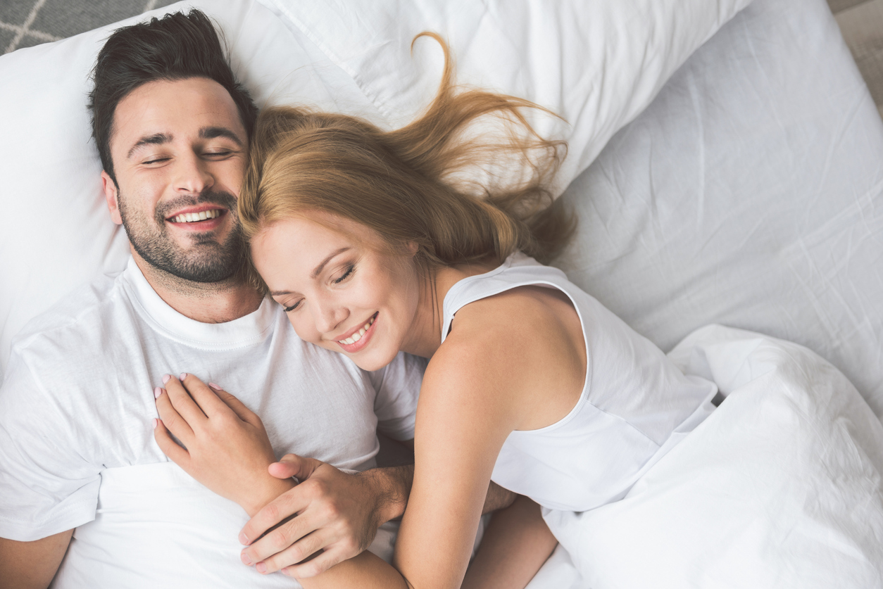 I am so happy with you. Top view portrait of cheerful young man and woman embracing while lying on bed. They are smiling with closed eyes