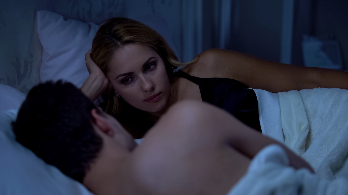 Offended woman looking with anger at boyfriend, lying in bed, revenge planning